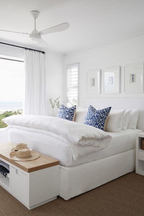 a modern beach bedroom in white, with a large bed, a storage bench and printed blue pillows plus a gorgeous sea view