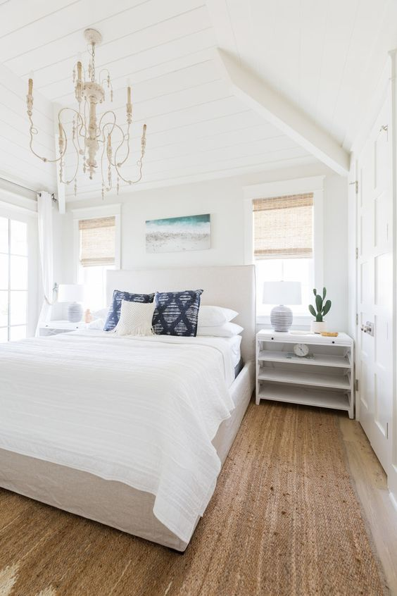 a modern beach bedroom with a jute rug, a white bed and nightstands, a vintage chandelier and a bright artwork