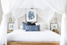a modern beach bedroom with a wooden bed, a jute rug, printed blue pillows, sea artworks and airy curtains plus Moroccan lamps