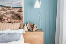 a modern beach bedroom with blue walls, a wooden bed, a statement artwork and printed and blue bedding