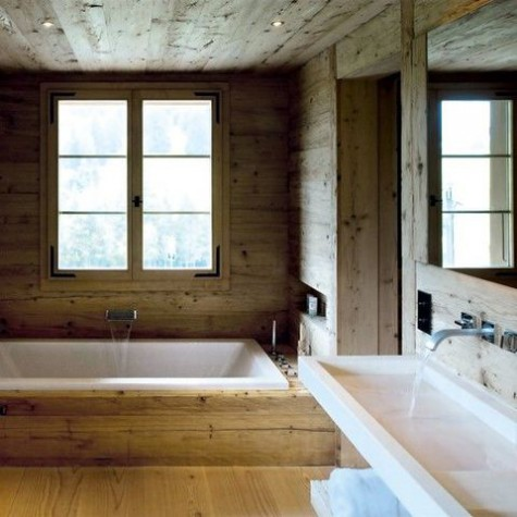 a modern chalet bathroom all clad with wood, a wall mounted sink, a built in tub and modern faucets