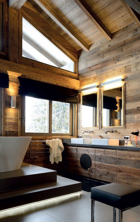 a modern chalet bathroom clad with light-colored wood, with touches of black, modern furniture and appliances