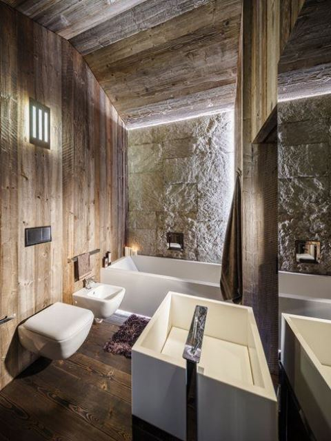 a modern chalet bathroom clad with reclaimed wood, with a stone wall, modenr appliances and built-in lights