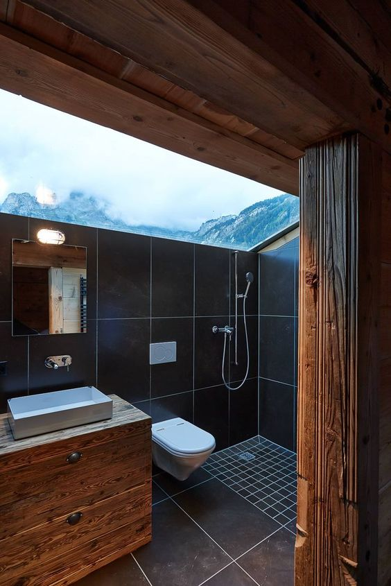 a modern chalet bathroom done with light-colored wood and black tiles and with a skylight to enjoy the views