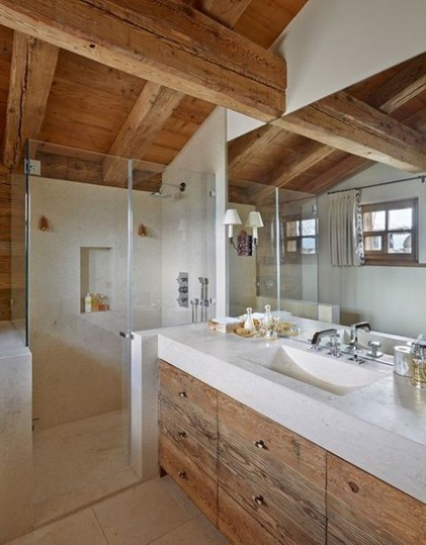 a modern chalet bathroom with light colored stone and wood, with a shower space and a large mirror