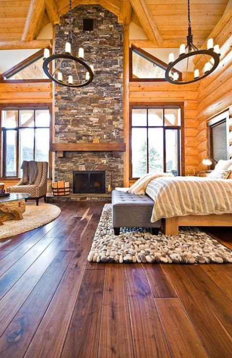 a modern chalet bedroom fully clad with wood, with a stone fireplace, candle chandeliers, comfy modern furniture