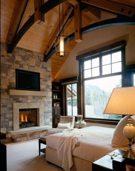 a modern chalet bedroom with a stoen clad fireplace, comfy refined furniture and touches of black for some drama