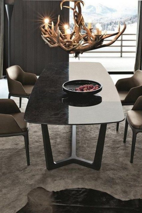 a modern chalet dining room with a sleek marble dining table, chairs, an antler chandelier and a faux fur rug
