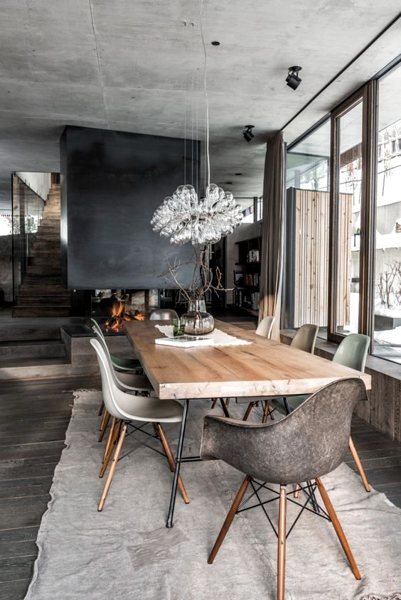 a modern chalet dining space with a wooden table, catchy chairs, a gorgeous bulb chandelier and a fireplace