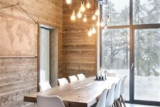 a modern chalet dining space with a wooden table, white chairs, an artwork and a creative lamp of bulbs
