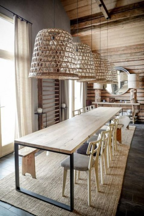 a modern chalet dining space with a wooden wall, a stone floor, wicker lamps and modern chairs and a table