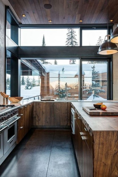 a modern chalet kitchen with glazed walls, wooden cabinets and a kitchen island, built-in lights and appliances