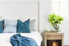 a modern coastal bedroom in neutrals, with a wooden nightstand, layered rugs, greenery and printed blue bedding for a coastal feel