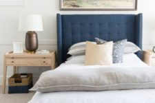 a modern coastal bedroom with a blue bed, printed textiles, a large artwork, wooden furniture, a basket for storage