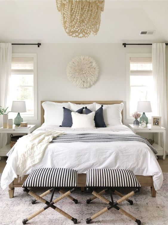 a modern coastal bedroom with a white bead chandelier, a wooden bed, striped stools, blue bedding and a faux fur decoration