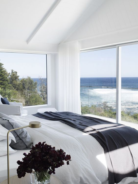 a modern coastal bedroom with glazed walls and a balcony, with white furniture and darker textiles in coastal colors