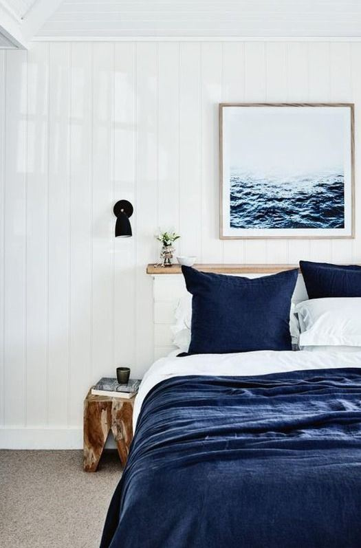 a modern coastal bedroom with navy and white bedding, a sea artwork, black sconces and a wooden stool