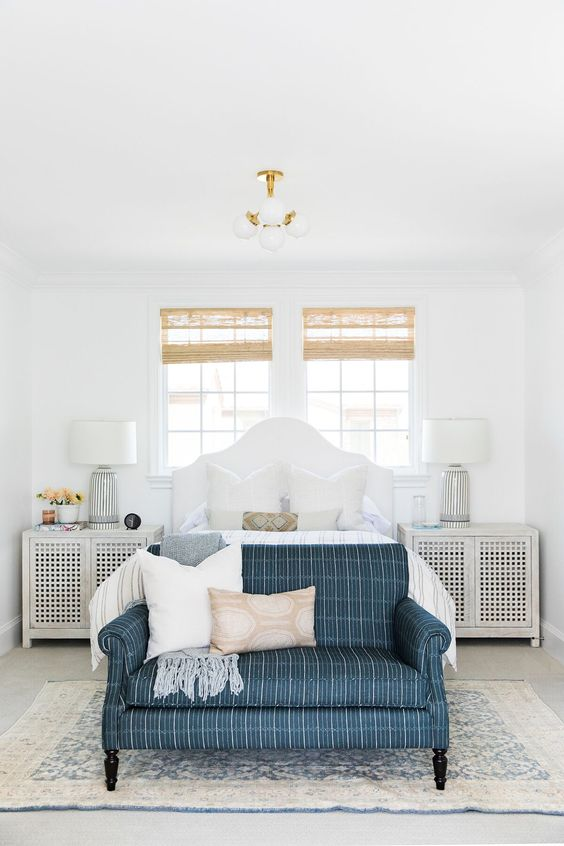 a modern coastal bedroom with wicker shades, a white bed and perforated nightstands, a blue sofa and printed bedding
