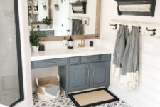 a modern farmhouse bathroom with a large mirror, a grey vanity, a shower, a tile floor and some cool decor