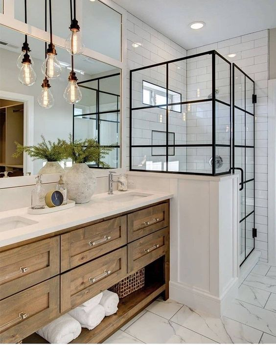 a modern farmhouse bathroom with a shower space with black framing, a wooden vanity, bulbs hanging and some greenery