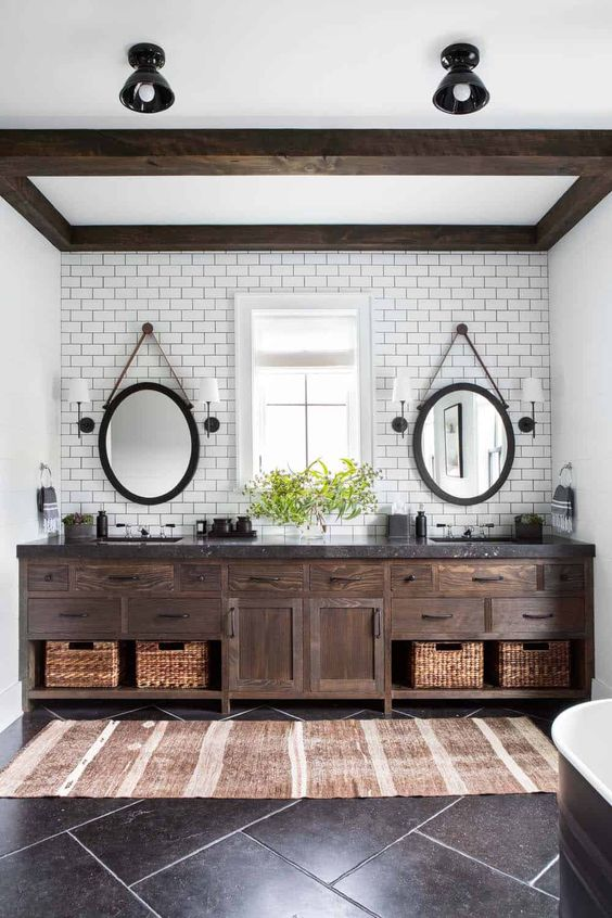 a modern farmhouse bathroom with subway tiles, a dark wooden frame on the ceiling and matching vanity plsu baskets