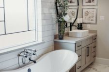 a modern farmhouse bathroom with white beadboard walls, a vintage tub, a wooden vanity and a black sconce