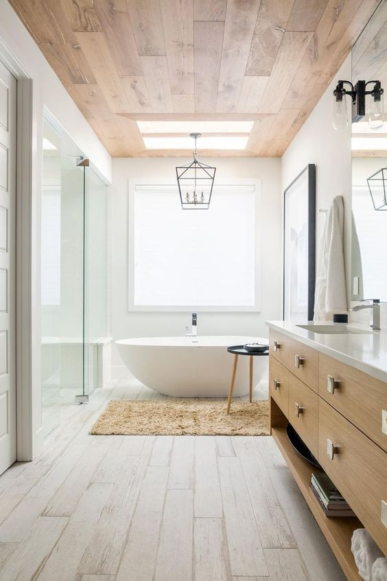 a modern farmhouse bathroom with white laminate floor and a stained laminate ceiling, a wooden vanity, vintage lamps and sconces