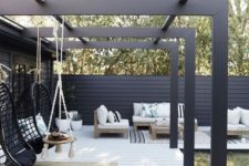 a modern monochromatic patio with black pendant chairs, boho pillows, simple wooden furniture with printed pillows