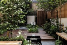 a modern natural backyard with a deck, wooden benches, a couple of waterfalls with pebbles and greenery