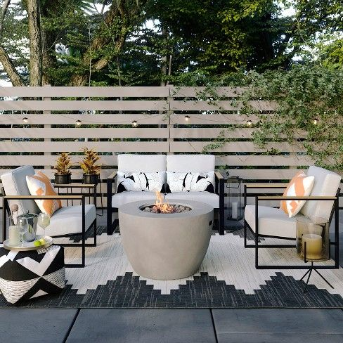 a modern patio with a concrete fire pit, comfy chairs and a sofa, printed textiles in black and white and lights