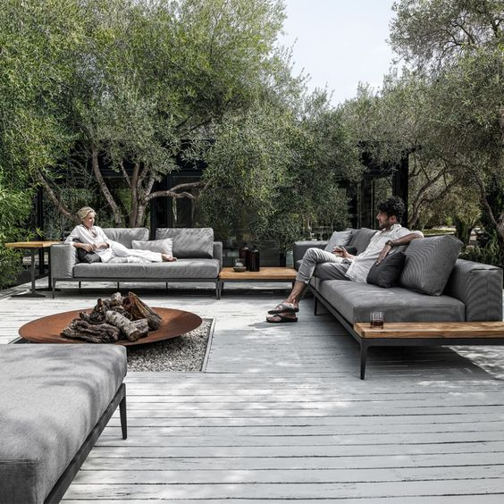 a modern patio with comfy grey sofas, a large fire pit, a white deck and trees around the space
