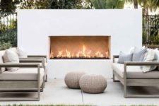 a modern patio with neutral furniture, a white built-in fireplace and wicker ottomans is welcoming