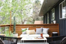 a modern patio with simple wooden and woven furniture, a white table, a grey rug and potted greenery and plants