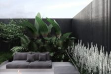 a modern tropical backyard with grey sofas on platforms, a fire pit and lots of lush greenery and blooms