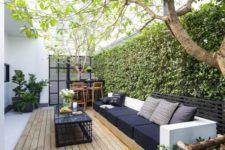 a modern welcoming backyard with a deck, s amll bar space, a large sofa and a black coffee table plus a living wall