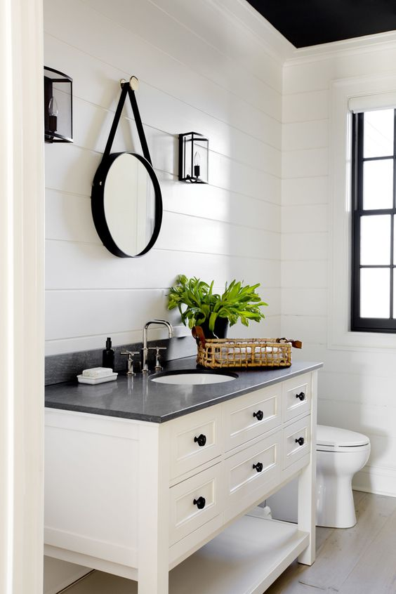 a monochromatic farmhouse powder room clad with white beadboard, with a two tone vanity, a vintage mirror and greenery
