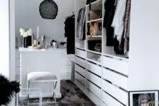 a monochromatic minimalist closet with a large storage unit with drawers, open compartments and a white vanity plus a stool