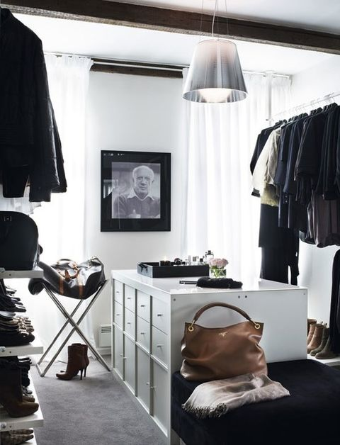 a monochromatic minimalist closet with open holders and shelves and a large white dresser and black ottoman