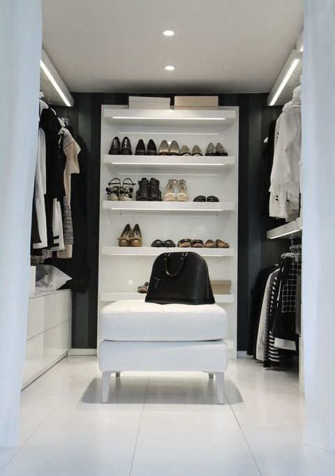 a monochromatic minimalist closet with open shelves, holders for hangers, white sideboards and lots of built in lights