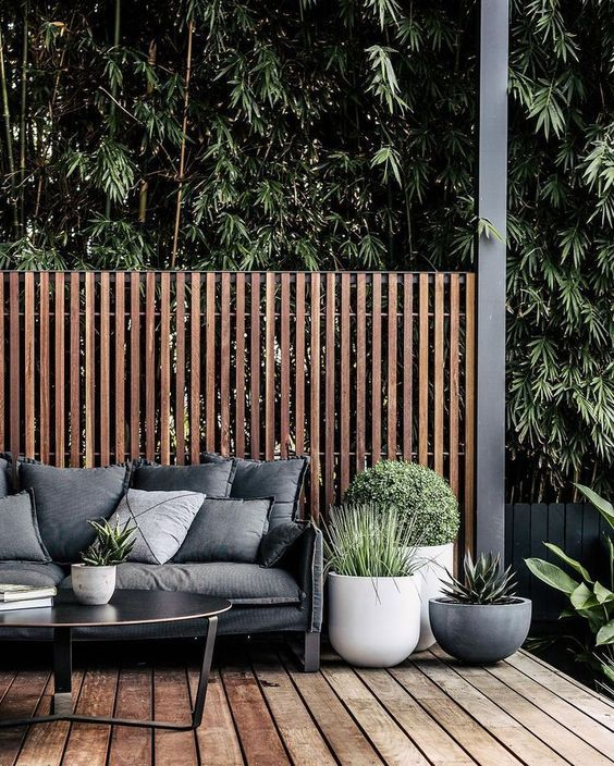 a monochromatic modenr backyard with a wooden deck, a black sofa and coffee table and large planters with greenery