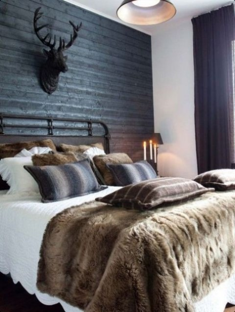 a moody chalet bedroom with a black wood clad wall, a vintage forged bed, faux fur pillows and black lamps