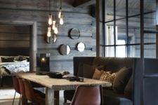 a moody chalet dining space with a large black sofa, pendant bulbs, a wooden table and leather chairs