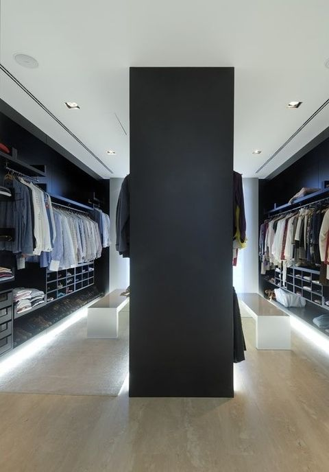 a moody minimalist closet in black and navy, white benches, holders, open and closed shelves plus built-in lights