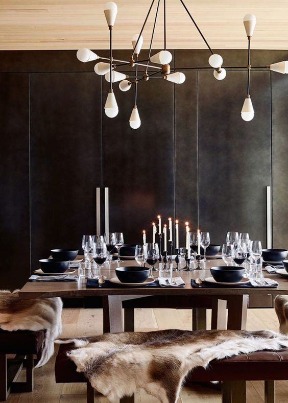 a moody modern chalet dining space with black walls, dark modenr furniture, a catchy chandelier and candles