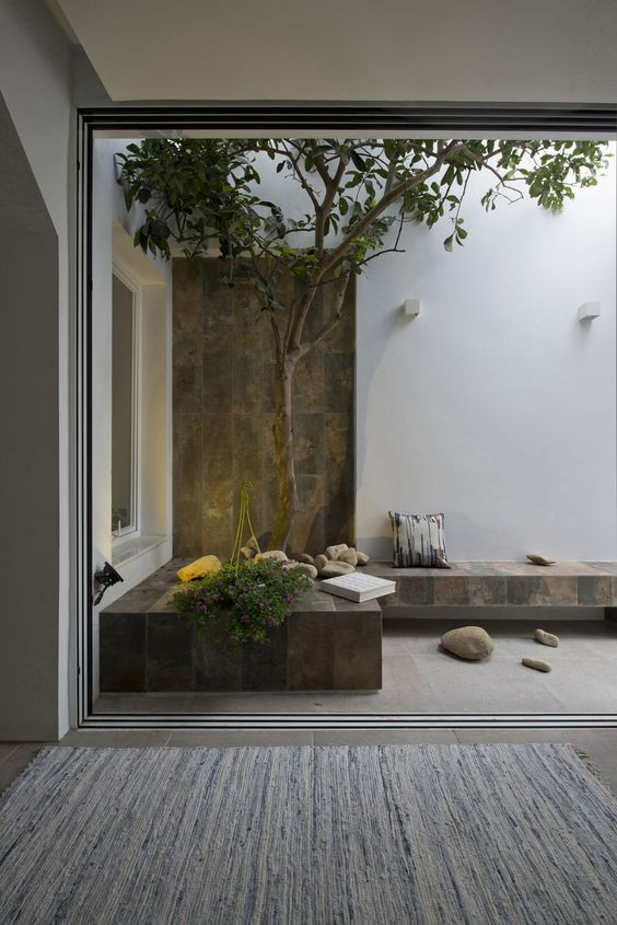 a natural yet minimalist patio with a stone bench, a tree, some greenery, rocks and a pillow is very peaceful