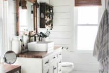 a neutral farmhouse bathroom clad with white beadboard, with white furniture and stained wood plus wicker shades