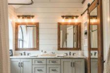 a neutral farmhouse bathroom with white beadboard, grey furniture, wood frame mirrors, sconces and a tub