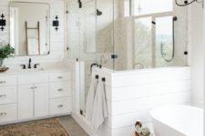 a neutral farmhouse bathroom with white beadboard, neutral tiles, a bathtub, a white vanity and black touches