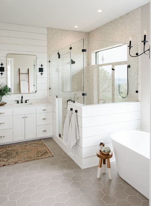 a neutral farmhouse bathroom with white beadboard, neutral tiles, a bathtub, a white vanity and black touches