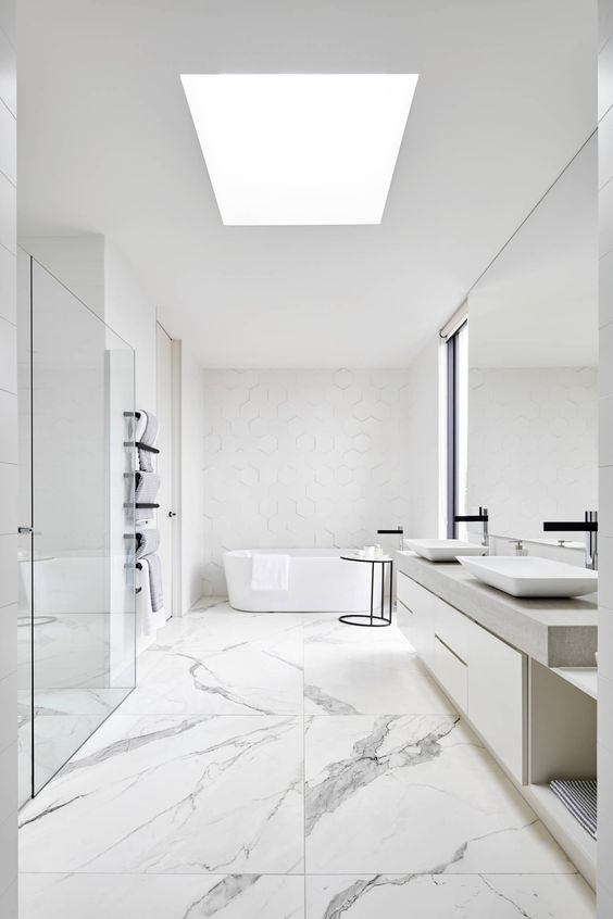 a neutral minimalist bathroom with catchy tiles of various sizes, a skylight, a large mirror and vanity, a tub and a shower space